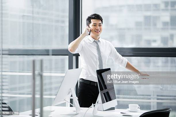 Young businessman on the phone in the office