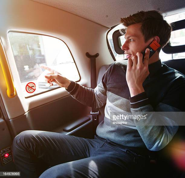 Young Businessman on the phone traveling in taxi