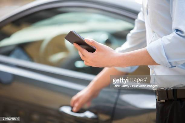 Young businessman opening car door