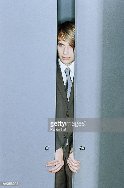 Young businessman opening doors