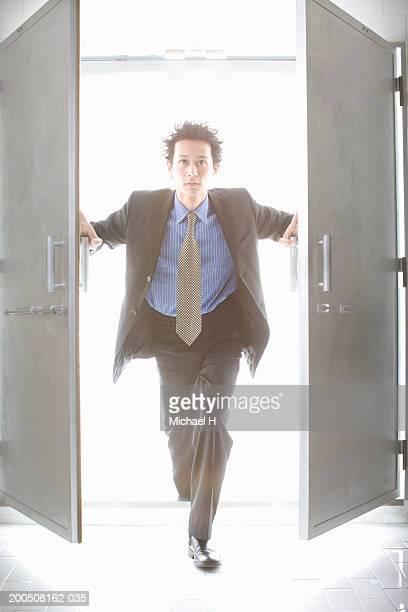 Young businessman opening double doors, portrait