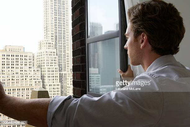 Young businessman opening window, facing office buildings in cityscape