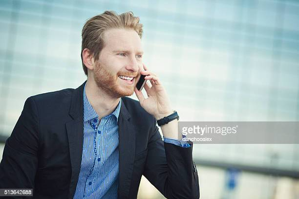Young businessman outdoors talking on the phone