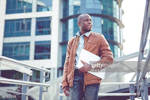 Junger Geschäftsmann vor Bürogebäude