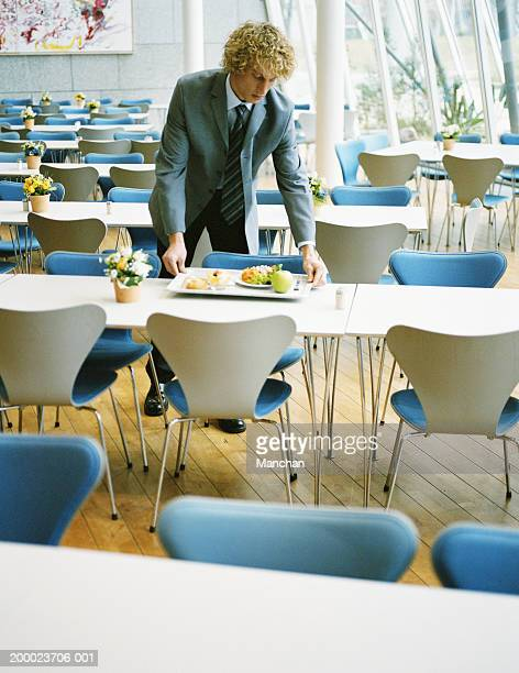 Young businessman placing tray on table in empty canteen