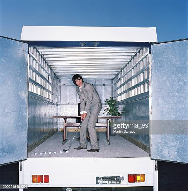 Young businessman playing golf in office, within lorry