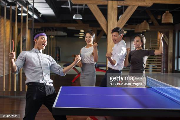 Young businessman playing ping pong