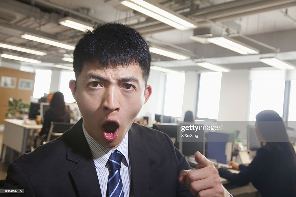 Young Businessman pointing and shouting, looking at camera : Stock Photo