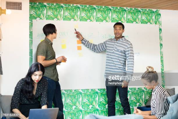 young businessman pointing at whiteboard in creative meeting room - heshphoto photos et images de collection