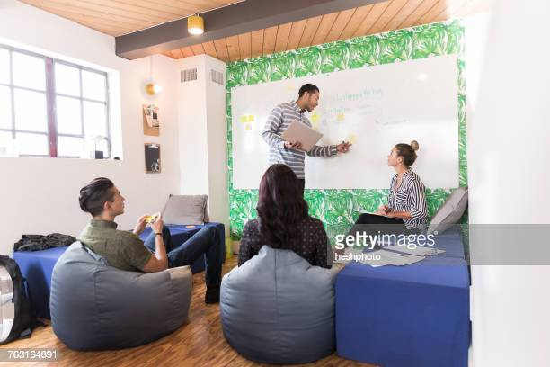 young businessman pointing at whiteboard in creative meeting room - heshphoto stock pictures, royalty-free photos & images