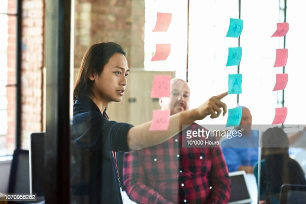 young businessman pointing to sticky note on window - thinking outside the box englische redewendung stock-fotos und bilder
