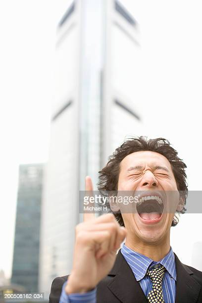 Young businessman pointing up, laughing, eyes closed