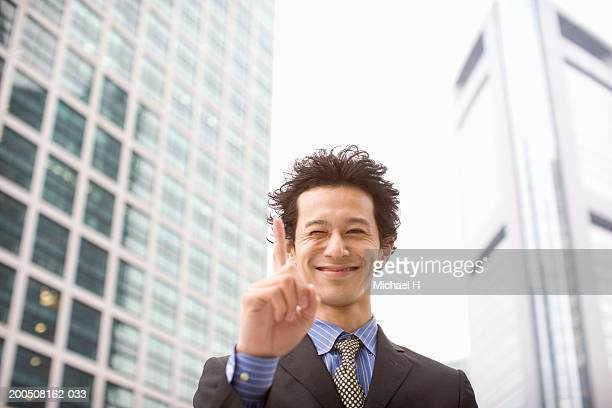 Young businessman pointing up, smiling, portrait
