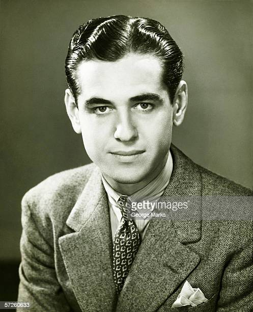 Young businessman posing in studio, (B&W), portrait
