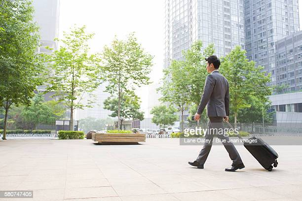 Young businessman pulling suitcase walking