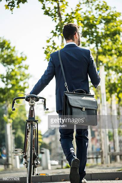 Young businessman pushing bicycle, holding smart phone