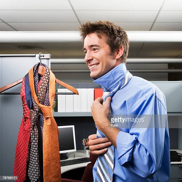 Young Businessman Putting on Necktie