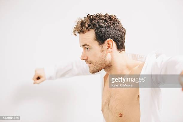 Young businessman putting on shirt in apartment