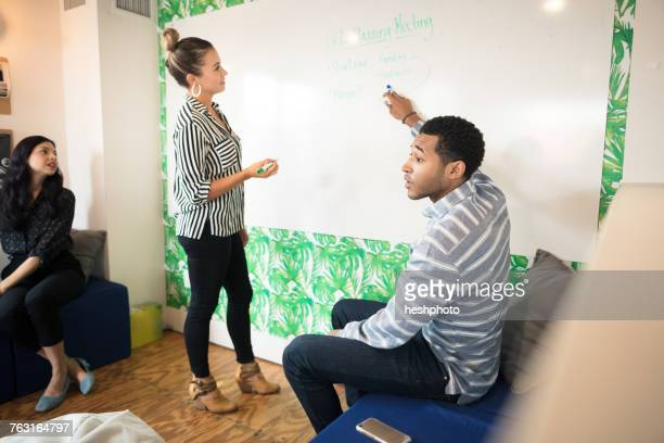 young businessman questioning during presentation in creative meeting room - heshphoto stock pictures, royalty-free photos & images