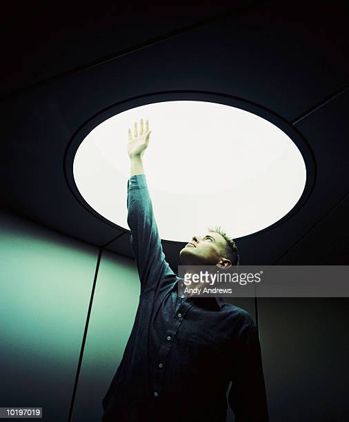Young businessman raising hand into light fitting