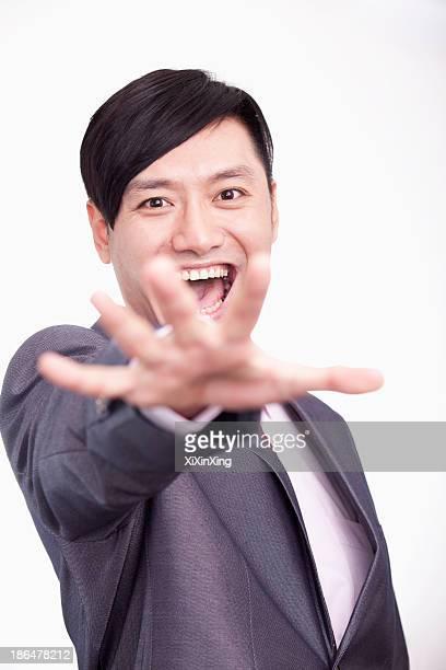 Young businessman reaching out towards camera, studio shot