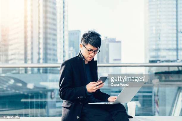 Young businessman reading message on phone while using computer outdoors