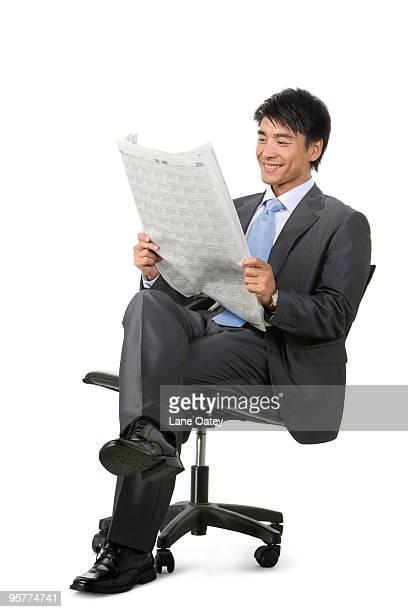 young businessman reading newspaper - フォーマルウェア ストックフォトと画像