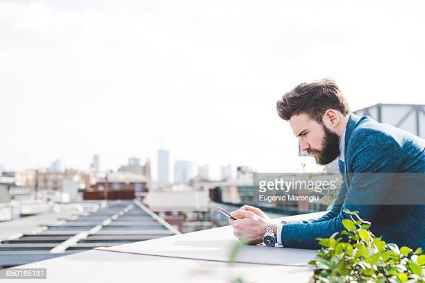 Young businessman reading smartphone text on office roof terrace