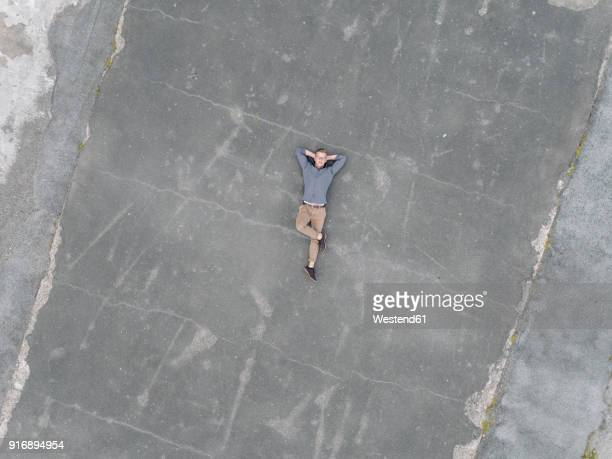 young businessman relaxing on tarmac, quadcopter viewquadcopter - lying down stock pictures, royalty-free photos & images