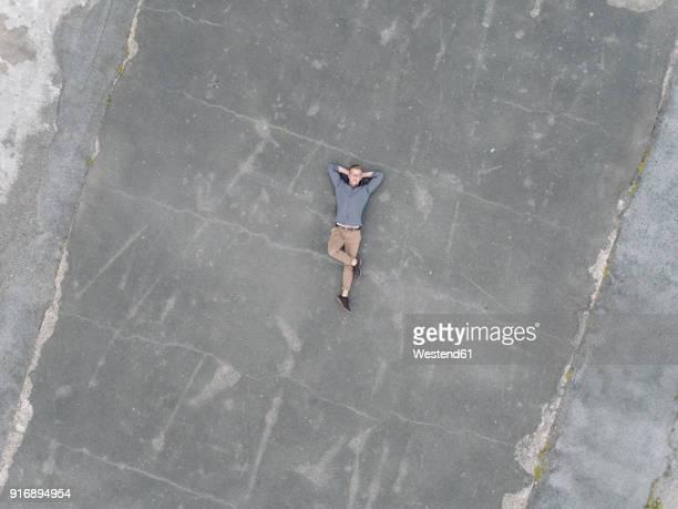 young businessman relaxing on tarmac, quadcopter viewquadcopter - lying down fotografías e imágenes de stock