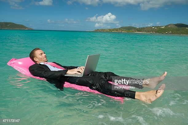 Jeune homme d'affaires de détente avec ordinateur portable travaillant à flotter dans l'eau tropicale