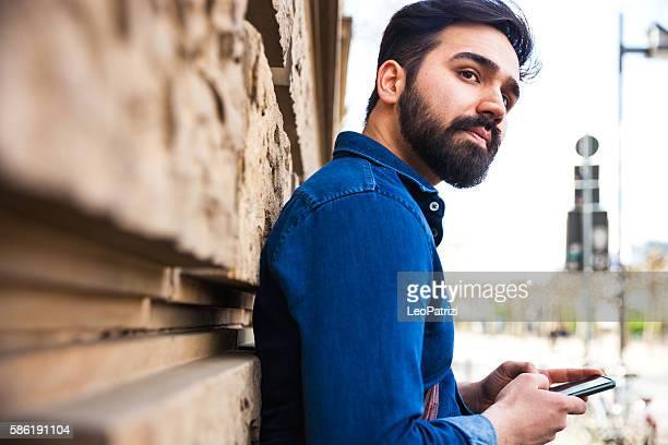 jeune homme d'affaires répondant à un texte sur mobile - homme arabe barbu photos et images de collection
