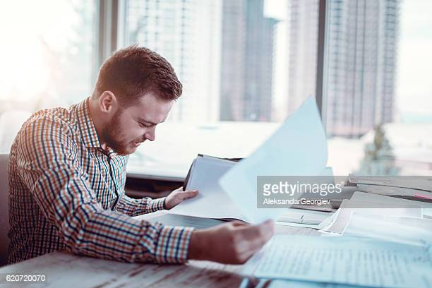 Young Businessman Reviewing Plans at Blue Prints on Desk