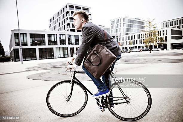 Young businessman riding bicycle, Munich, Bavaria, Germany
