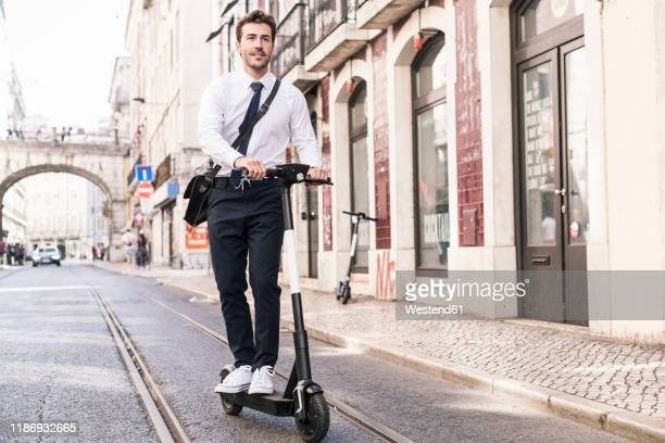 young businessman riding e-scooter in the city, lissabon, portugal - electric scooter stock pictures, royalty-free photos & images
