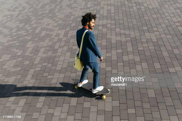 young businessman riding skateboard on a square - independência imagens e fotografias de stock