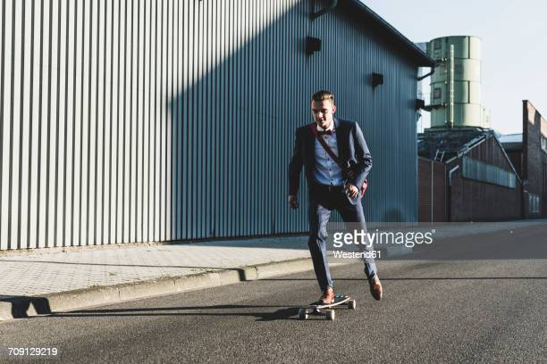 Young businessman riding skateboard on the street