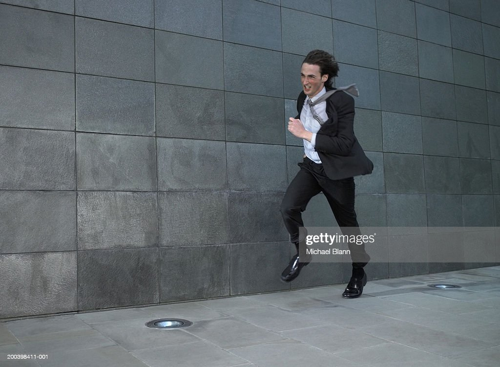Young businessman running against wind : Stock Photo