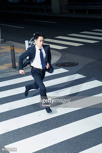 Young businessman running on crossroad