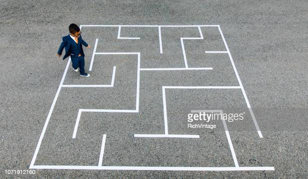 young businessman running through maze. - skill stock pictures, royalty-free photos & images