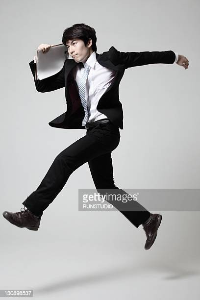 young businessman running with a binder