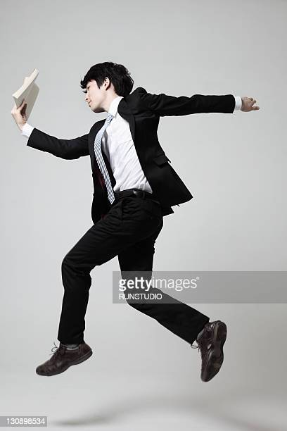 young businessman running with a book