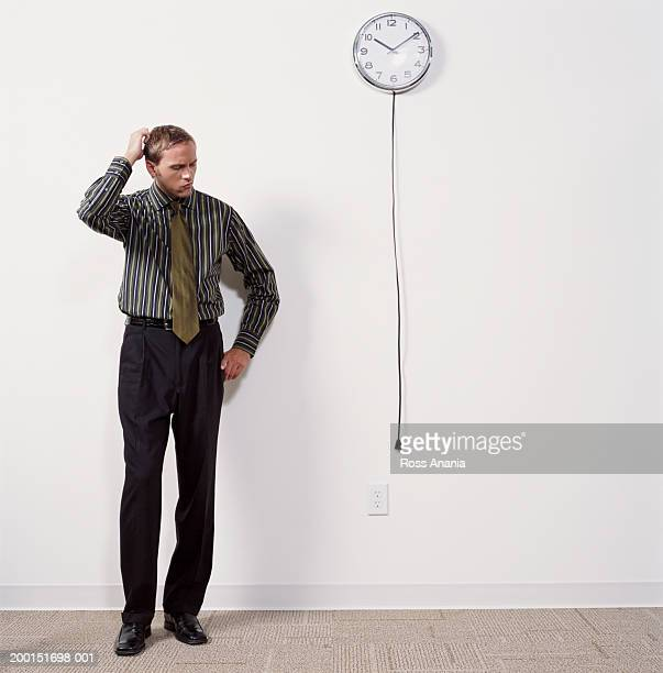 Young businessman scratching head, looking at unplugged wall clock