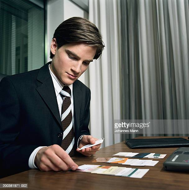 Young businessman setting out business cards on desk