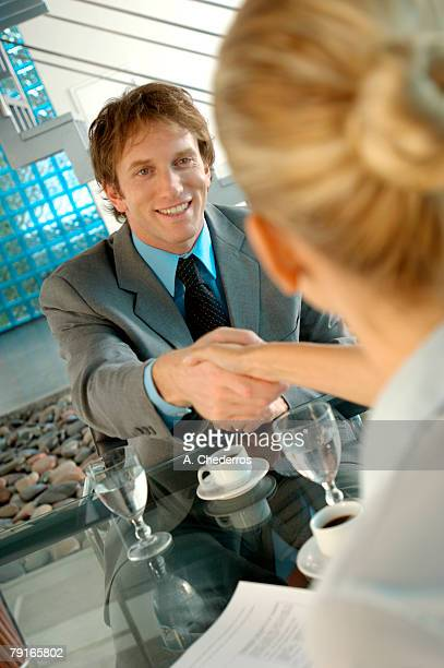 Young businessman shaking hand with businesswoman in office