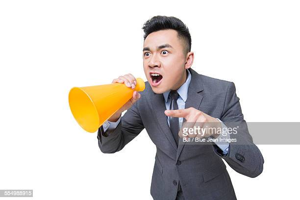 Young businessman shouting into megaphone