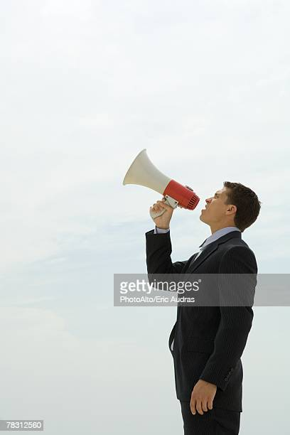 Young businessman shouting into megaphone, side view