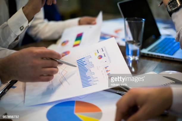 jovem empresário, mostrando gráficos por caneta - explicar - fotografias e filmes do acervo