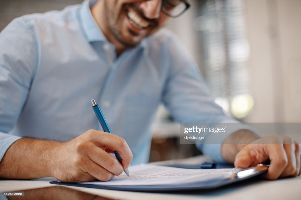 Young businessman signing a contract : Stock Photo
