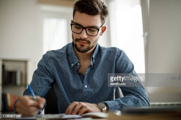 young businessman signing documents - damircudic stock photos and pictures